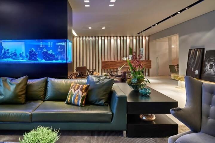 Sala de estar com sofá de couro verde e aquário Projeto de Gislene Lopes