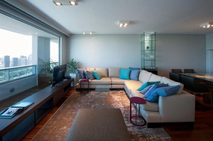 Sala de estar com sofá em L amplo branco com almofadas em tons de azul Projeto de Estúdio Sespede