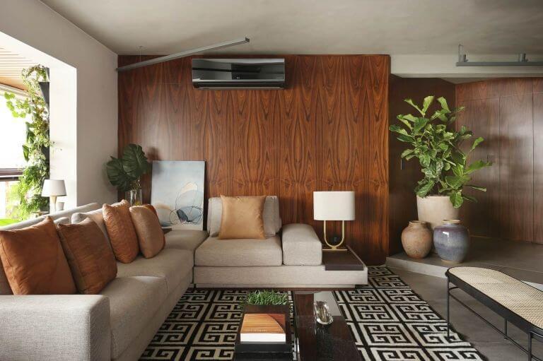 Sala de estar com sofá em L bege e tapete geométrico Projeto de Quattrino Arquitetura