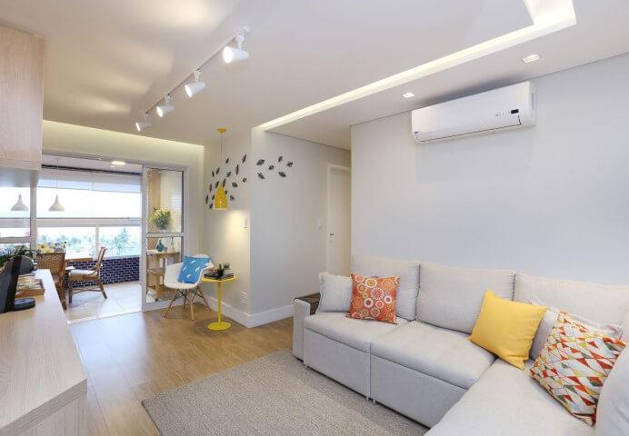 Sala de estar com sofá em L branca integrada a cantinho da leitura Projeto de Pagama Arquitetura