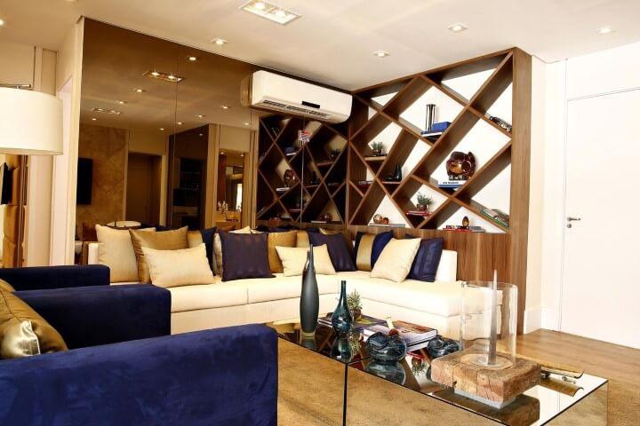 Sala de estar com sofá em L branco com estante de madeira embutida Projeto de Marel