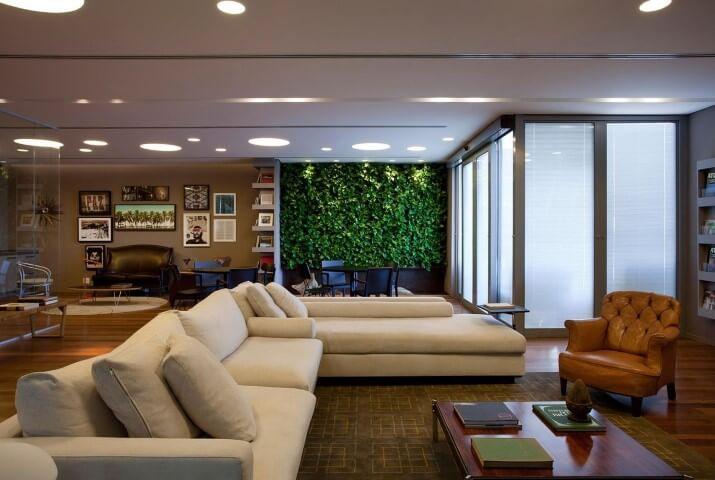 Sala de estar com sofá em L branco e poltrona marrom de couro Projeto de AMC Arquitetura