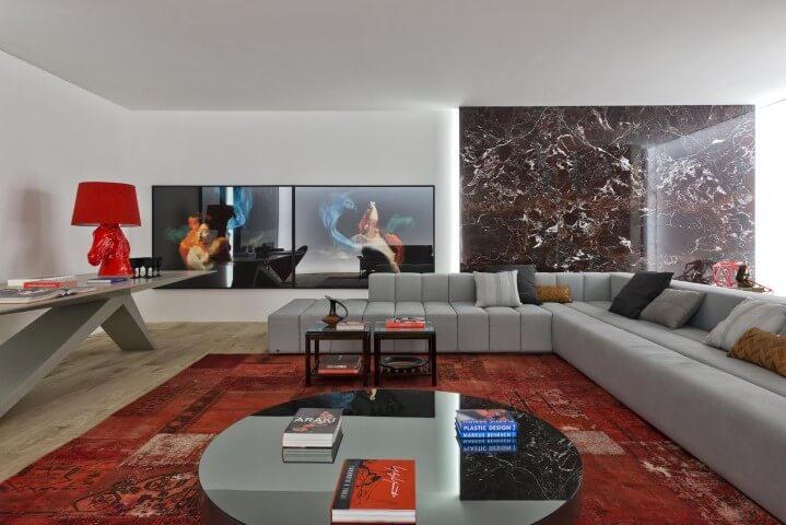 Sala de estar com sofá em L cinza amplo e tapete vermelho Projeto de Casa Cor 2016
