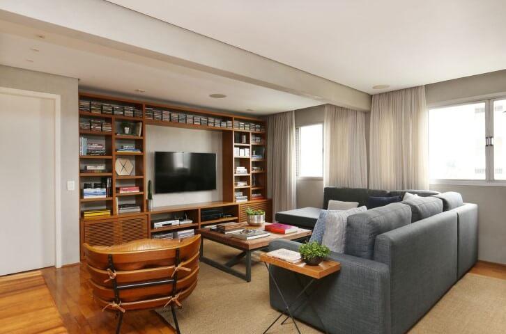 Sala de estar com sofá em L cinza e demais móveis de madeira Projeto de Oliveira Arquitetura