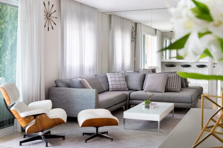 Sala de estar com sofá em L cinza e poltrona Eames branca Projeto de GF Projetos