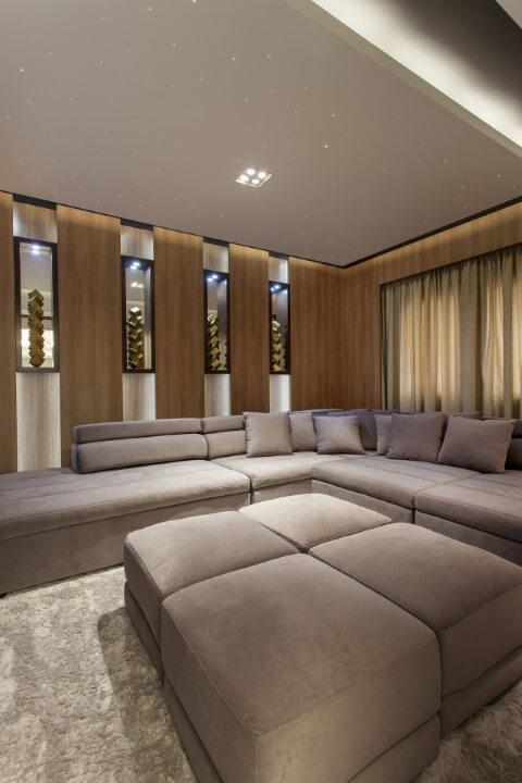 Sala de estar com sofá em L cinza e puffs grandes no centro Projeto de Iara Kilaris