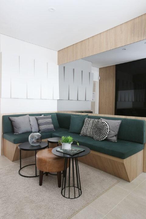 Sala de estar com sofá em L com estrutura de madeira e almofadas verdes Projeto de Anna Maria Parisi