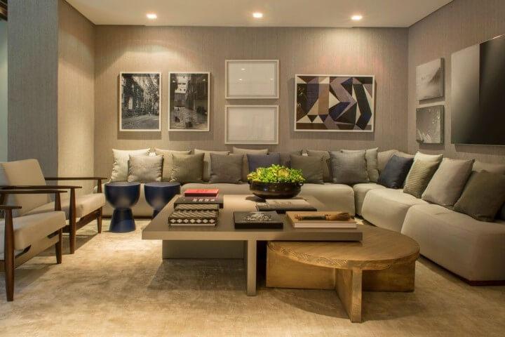 Sala de estar com sofá em L e várias almofadas e quadros decorativos Projeto de Triplex Arquitetura