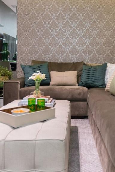 Sala de estar com sofá em L encostado em meia parede Projeto de Helena Koki