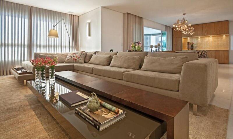 Sala de estar com sofá em L grande bege escuro Projeto de Eduarda Correa