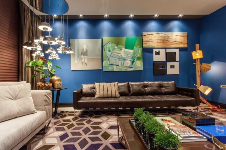 Sala de estar com sofa de couro marrom em parede azul com uadros diferentes Projeto de Juliana Pippi