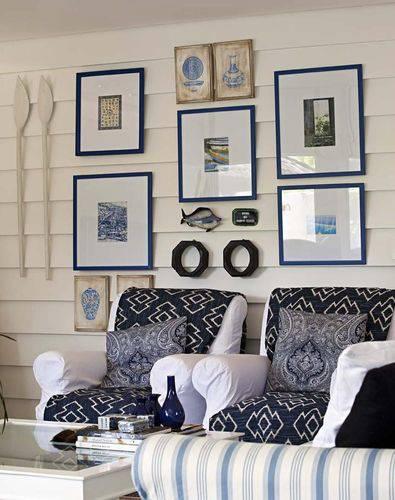 Sala de estar com temática de praia e molduras para quadro azuis com paspatur branco Projeto de Marcelo Brito