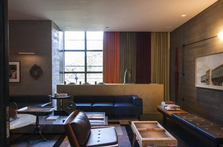 Sala de estar moderna com cortinas coloridas e sofá de couro preto Projeto de Casa Cor 2016