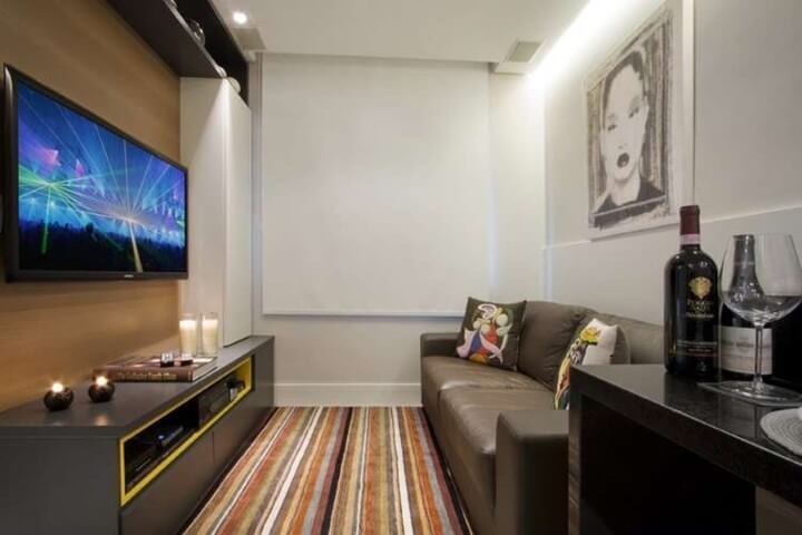 Sala de estar pequena com sofá de couro, tapete listrado colorido e painel para TV de madeira Foto de Eduardo Imóveis