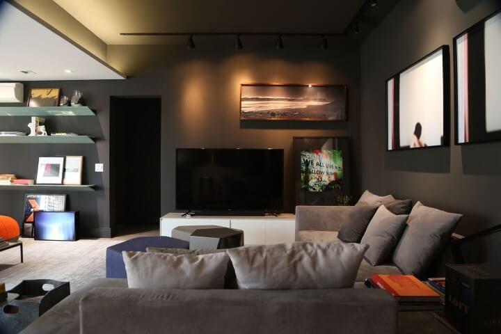 Sala de estar preta com sofá em L pequeno e almofadas cinzas Projeto de Triart Arquitetura
