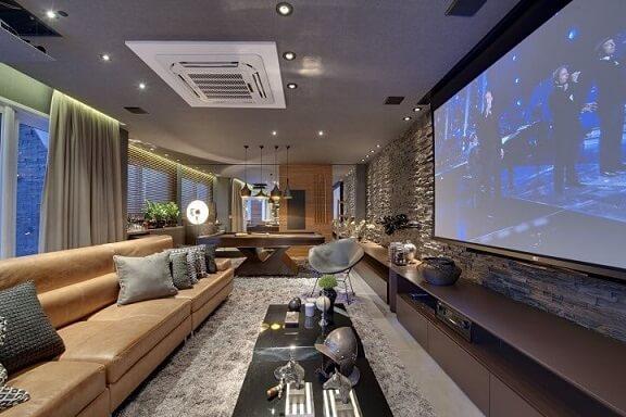 Sala de estar sofisticada com sofá de couro caramelo claro e parede canjiquinha Projeto de Carla Felippi