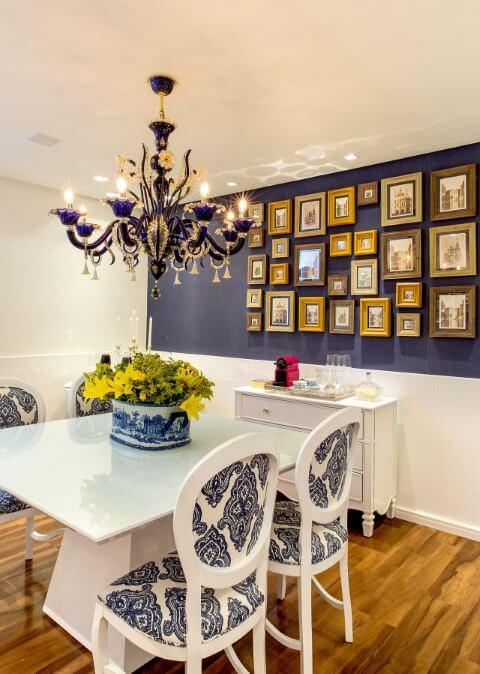 Sala de jantar com parede azul e várias molduras para quadros combinando entre si e com a decoração Projeto de Milla Holtz