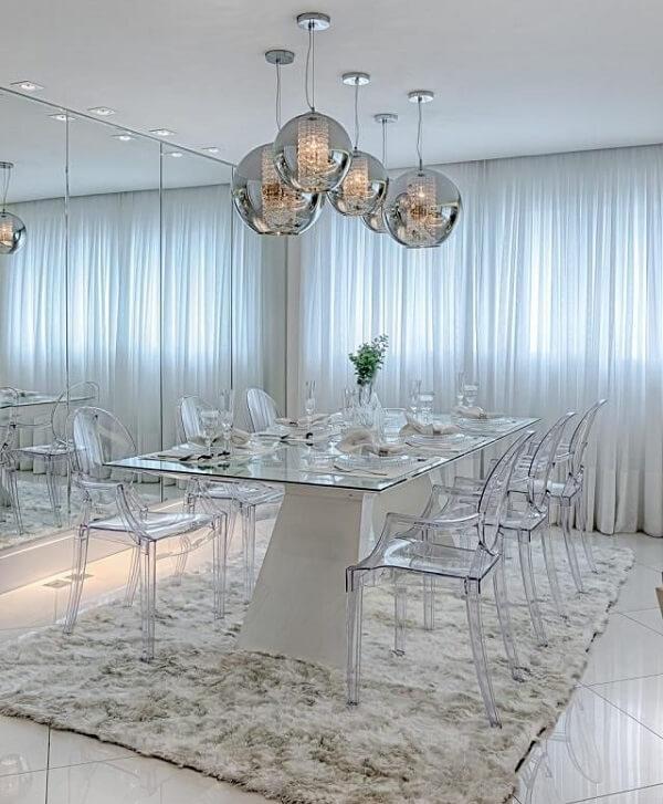 Sala de jantar com parede espelhada e luminárias de teto metálicas