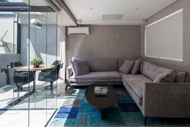 Sala integrada à varanda com sofá em L cinza e mesa de centro preto Projeto de Tria Arquitetura