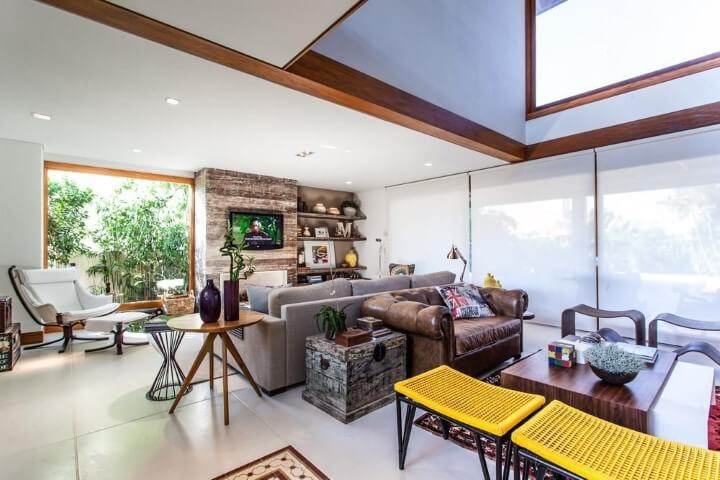 Sala integrada bem iluminada com sofá de couro marrom pequeno Projeto de Juliana Pippi