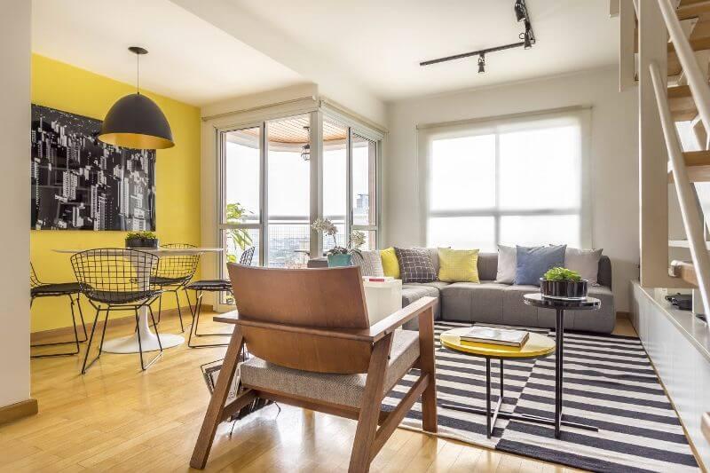 Sala integrada com parede amarela e sofá cinza e almofadas coloridas Projeto de Hildebrand Silva Arquitetura