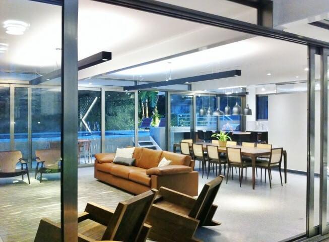 Sala integrada com sofá de couro caramelo e poltronas de madeira Projeto de Adriana Fornazari