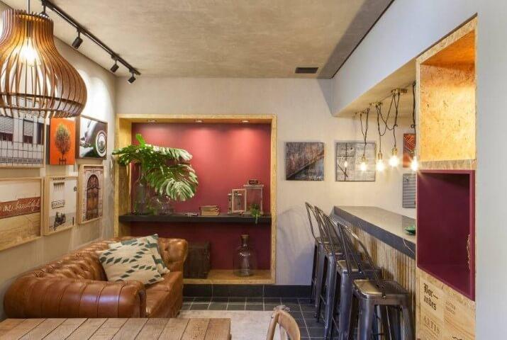 Sala integrada com sofá de couro com iluminação sobre ele Projeto de Casa Cor Franca 17