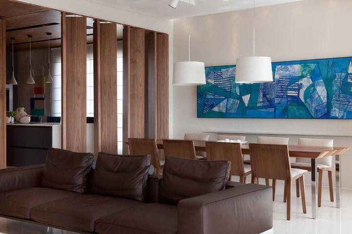 Sala integrada com sofá de couro escuro e mesa longa de madeira Projeto de Patricia Martinez