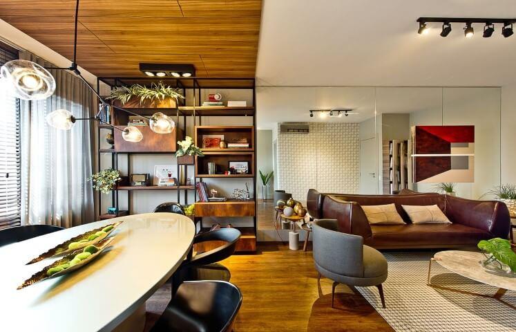 Sala integrada com sofá de couro escuro e poltrona cinza Projeto de Espaço do Traço