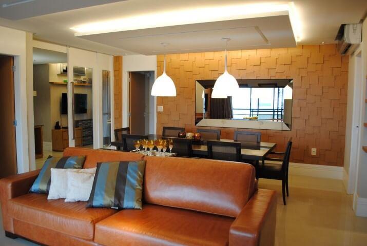 Sala integrada com sofá de couro marrom e almofadas Projeto de Oggi Arquitetura