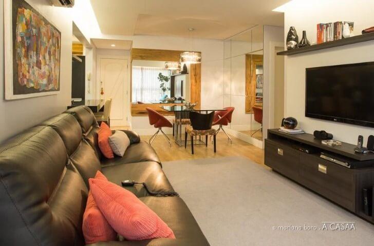 Sala integrada com sofá de couro preto e almofadas vermelhas Projeto de Rico Mendonça