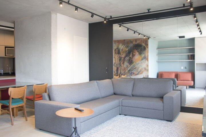 Sala integrada com sofá em L cinza e mesa de jantar atrás Projeto e Monica Spada Durante