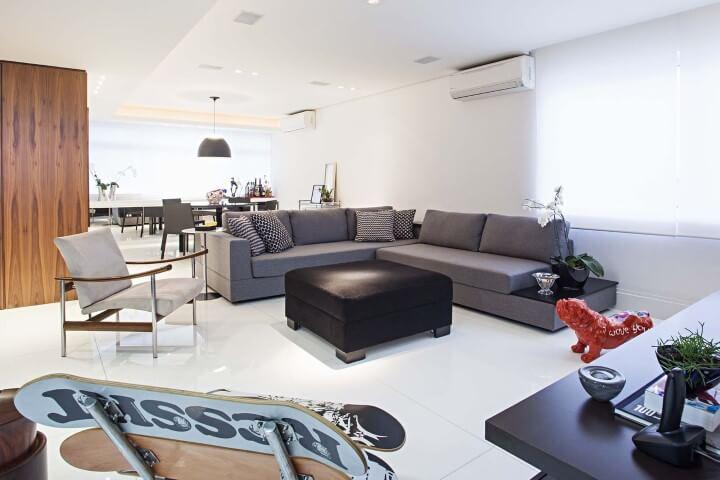 Sala integrada com sofá em L e mesa de jantar atrás Projeto de Korman Arquitetos