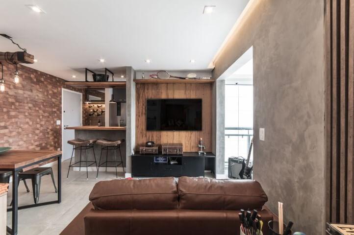 Sala pequena integrada com sofá de couro marrom e muitos tons de marrom Projeto de Pietro Terlizzi
