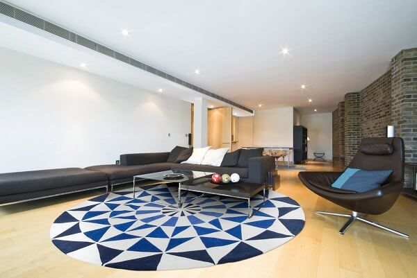 Sala de estar com tapete redondo geométrico e poltrona de couro preto