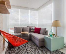Varanda com sofá em L cinza pequeno e cadeira string vermelha Projeto de Duda Senna