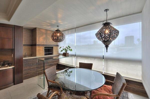 Varanda gourmet com bancada de vidro e luminárias de teto robustas