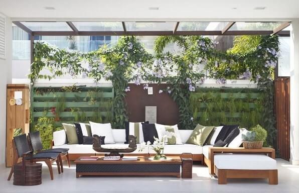 Varanda gourmet com sofá em L branco e estrutura de madeira Projeto de Angela Meza