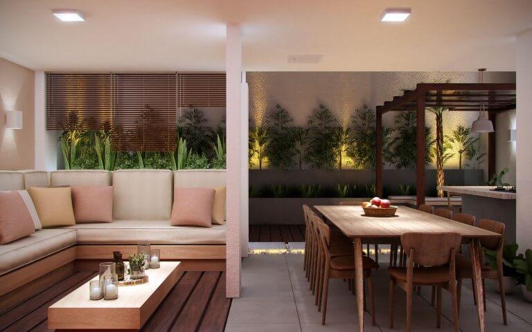 Varanda gourmet com sofá em L e almofadas em cores pastel Projeto de Amora Arquitetura