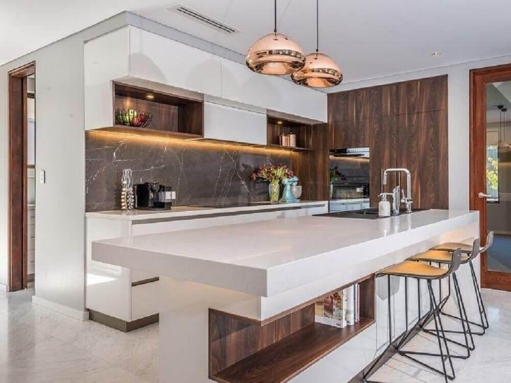 cozinha moderna decorada com pendentes sobre bancada nanoglass e iluminação embutida em armário aéreo Foto Letícia Borges