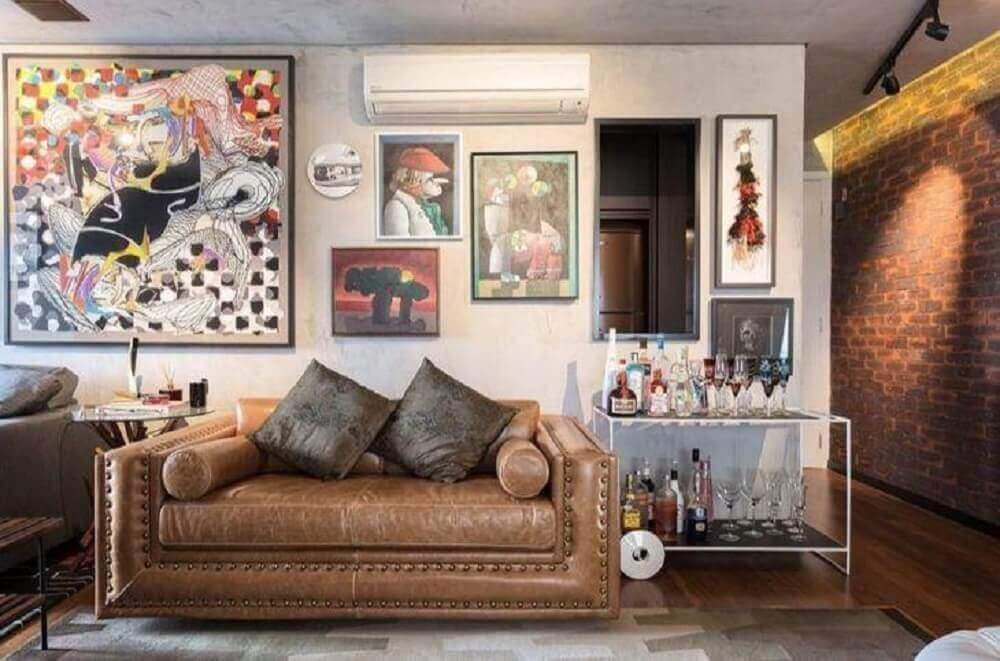 decoração com muitos quadros e sofá de couro para sala pequena Foto Clarice Semerene