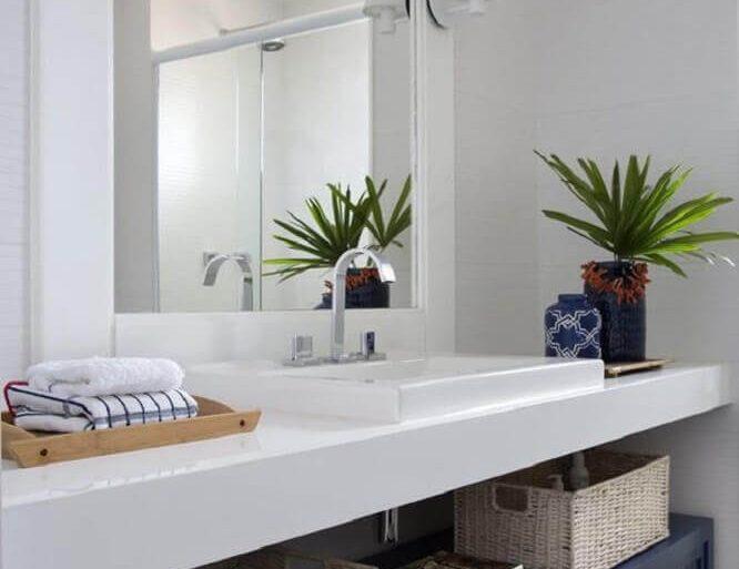 decoração de banheiro com bancada nanoglass branco e armário azul  Foto El' Lefébien