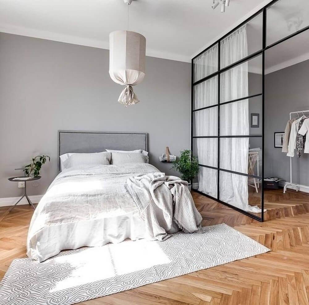 decoração minimalista para quarto com closet com parede divisória de vidro e piso de madeira Foto The Holk