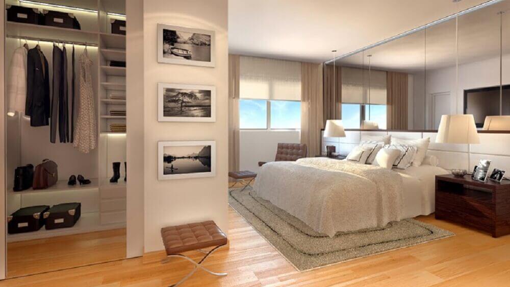modelo de quarto de casal com closet pequeno decorado com piso de madeira e parede espelhada Foto Estéfany Furtado