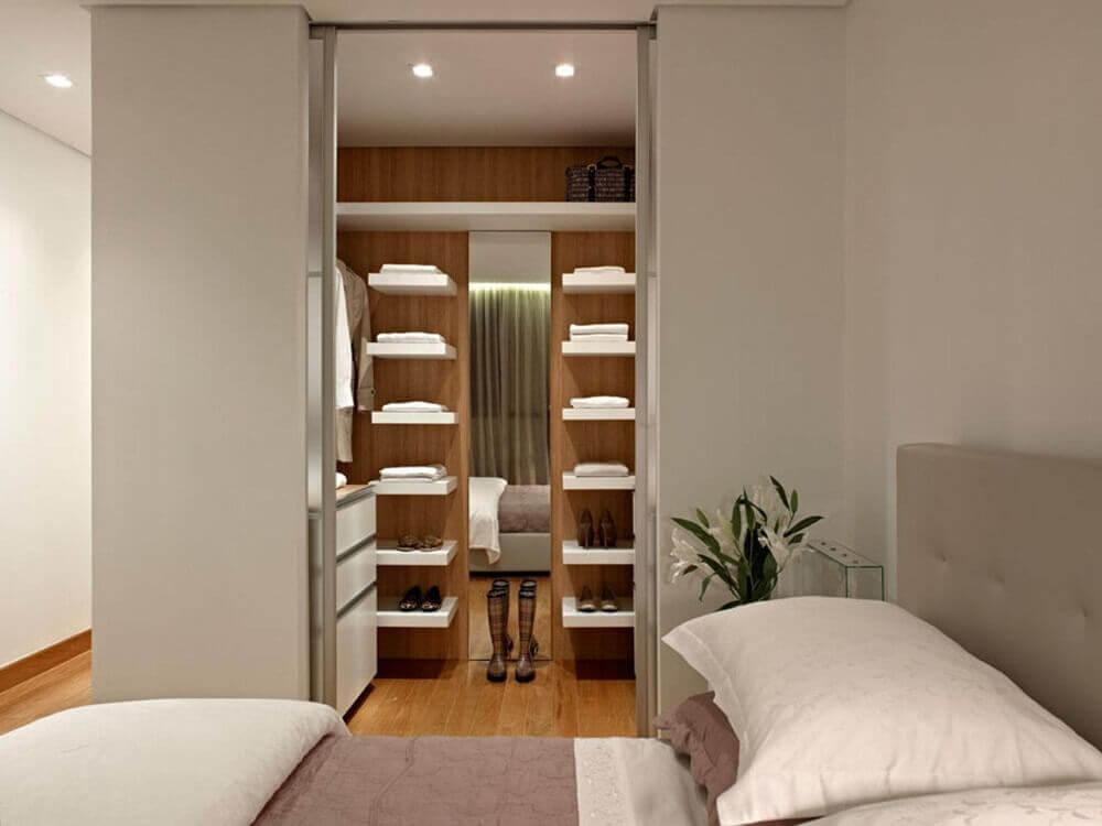 quarto com closet pequeno com revestimento de madeira e prateleiras brancas Foto Graziella Nicolai