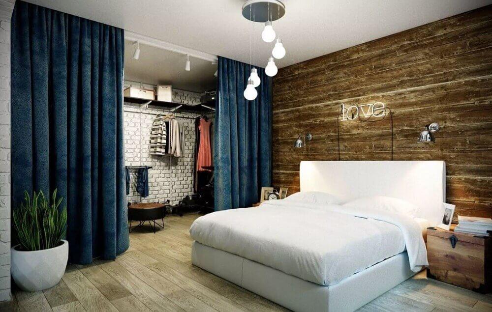 quarto de casal com closet com divisória de cortina azul e parede de tijolinho branco Foto Yandex