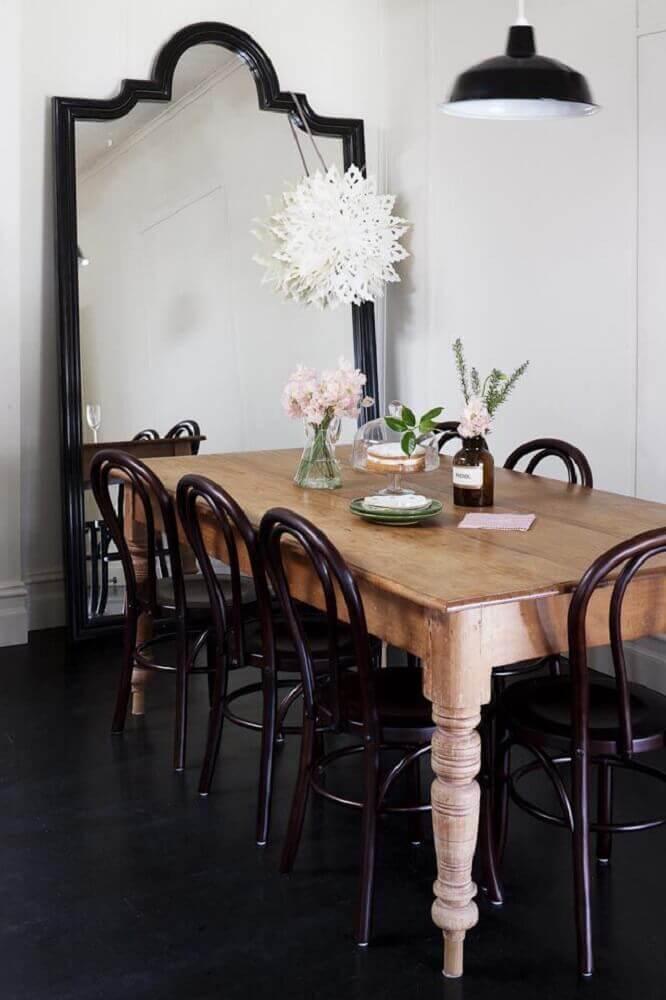 sala de jantar decorada com mesa de madeira e espelho grande com moldura preta Foto Pinterest