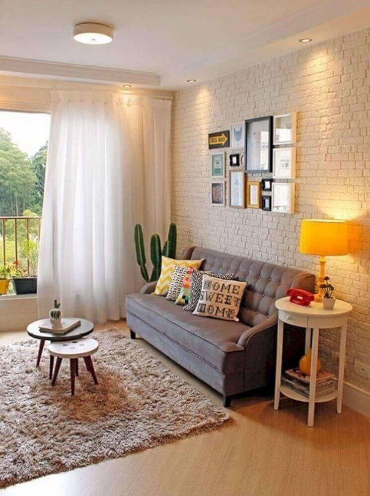 sofá cinza para sala pequena decorada com parede de tijolinho e vaso de cacto Foto Futurist Architecture