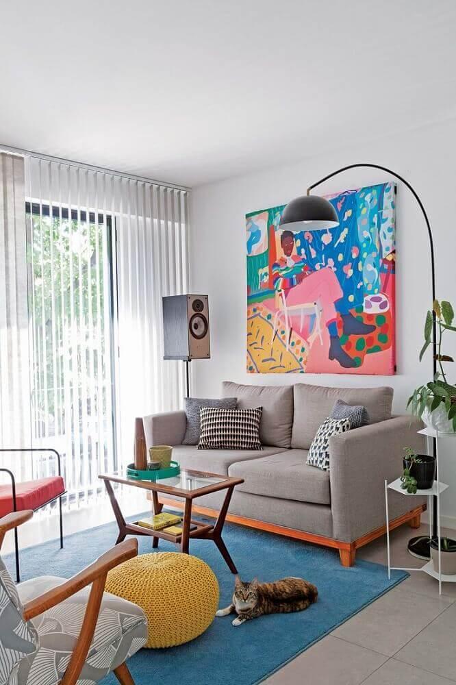 sofá para sala pequena decorada com quadro grande e puff de crochê amarelo Foto Pinterest