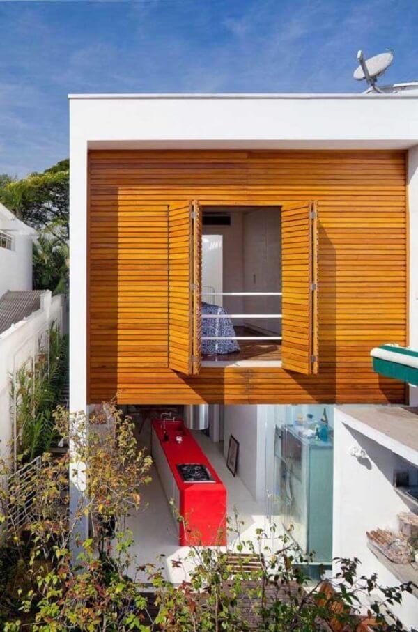 A platibanda branca se contrasta com a parede revestida em madeira